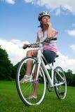 Muchacha bonita que se sienta en su bicicleta Fotos de archivo libres de regalías