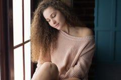 Muchacha bonita que se sienta en un alféizar Imagenes de archivo