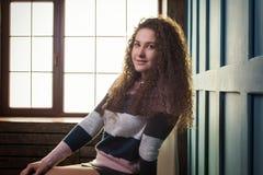 Muchacha bonita que se sienta en una silla contra la ventana Fotografía de archivo libre de regalías