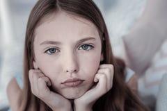Muchacha bonita que siente abajo en la boca Foto de archivo libre de regalías