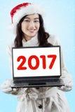 Muchacha bonita que sostiene el ordenador portátil con 2017 Fotos de archivo