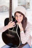 Muchacha bonita que sostiene la guitarra Imagen de archivo libre de regalías