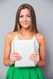 Muchacha bonita que sostiene la tableta Imágenes de archivo libres de regalías