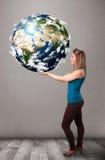 Muchacha bonita que sostiene la tierra del planeta 3d Imágenes de archivo libres de regalías