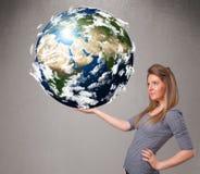 Muchacha bonita que sostiene la tierra del planeta 3d Fotos de archivo