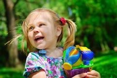 Muchacha bonita que sostiene los nuevos juguetes para la salvadera al aire libre Imágenes de archivo libres de regalías