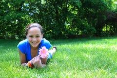 Muchacha bonita que sostiene una flor Foto de archivo