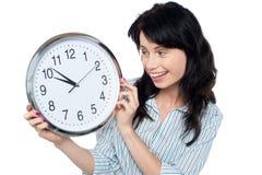 Muchacha bonita que sostiene y que mira el reloj de pared Foto de archivo libre de regalías
