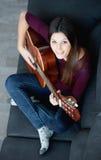 Muchacha bonita que toca la guitarra en el sofá Visión desde arriba Imagenes de archivo