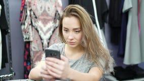 Muchacha bonita que toma el selfie en una tienda de ropa 4K almacen de video
