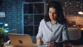 Muchacha bonita que trabaja con el ordenador portátil en la noche en la escritura sonriente de la oficina en cuaderno almacen de metraje de vídeo