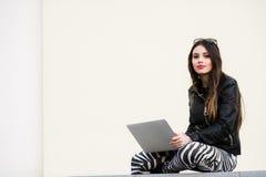 Muchacha bonita que trabaja con el ordenador portátil que se sienta en el muro de cemento al aire libre en el campus universitari Foto de archivo libre de regalías