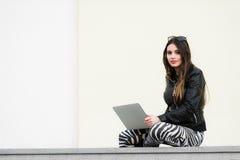 Muchacha bonita que trabaja con el ordenador portátil que se sienta en el muro de cemento al aire libre en el campus universitari Imagen de archivo libre de regalías