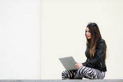 Muchacha bonita que trabaja con el ordenador portátil que se sienta en el muro de cemento al aire libre en el campus universitari Fotos de archivo libres de regalías