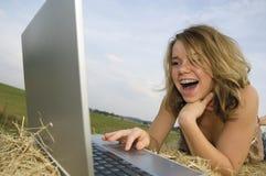 Muchacha bonita que trabaja en la computadora portátil imagenes de archivo