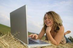 Muchacha bonita que trabaja en la computadora portátil imagen de archivo libre de regalías