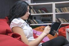 Muchacha bonita que trabaja en la PC de la tableta imagen de archivo libre de regalías