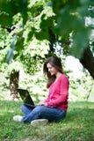 Muchacha bonita que usa el ordenador portátil en parque Imagenes de archivo