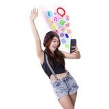 Muchacha bonita que usa el teléfono móvil para utilizar medios sociales Fotografía de archivo libre de regalías