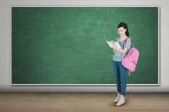 Muchacha bonita que usa la tableta en la sala de clase Foto de archivo libre de regalías