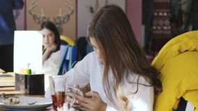 Muchacha bonita que usa smartphone en café Slolwy almacen de metraje de vídeo