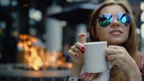 Muchacha bonita 30s en vidrios calificados que bebe té en el café de la calle de la ciudad almacen de video
