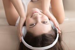 Muchacha bonita sonriente en los auriculares que mienten en el sofá, portra del headshot Imágenes de archivo libres de regalías