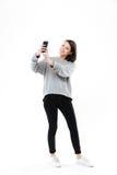 Muchacha bonita sonriente que coloca y que toma el selfie en el teléfono móvil Fotografía de archivo libre de regalías