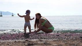Muchacha bonita sonriente que juega con su hijo en la arena en la playa, cámara lenta almacen de metraje de vídeo