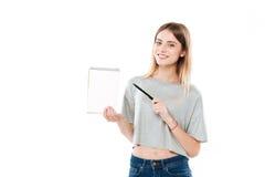 Muchacha bonita sonriente que señala la pluma en un cuaderno del papel en blanco Imagen de archivo