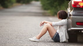 Muchacha bonita triste en el camino después del accidente de tráfico almacen de video