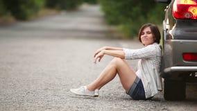 Muchacha bonita triste que se sienta en el camino después de accidente de tráfico almacen de metraje de vídeo
