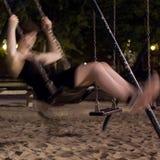 Muchacha borrosa en un oscilación en la noche Imagen de archivo