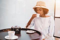 Muchacha brasileña con la leva del vintage en café de consumición del café Fotos de archivo