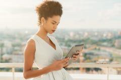 Muchacha brasileña en el balcón de la alta subida con la tableta digital Imágenes de archivo libres de regalías
