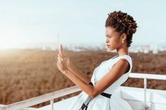 Muchacha brasileña en el tejado que toma las fotos vía la PC de la tableta Fotos de archivo
