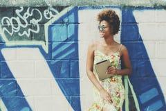 Muchacha brasileña negra hermosa joven con la tableta digital Imagen de archivo