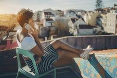 Muchacha brasileña que llama por teléfono en el tejado en Lisboa Fotos de archivo libres de regalías