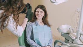 Muchacha brillante atractiva en una silla dental que sonríe de par en par en la cámara Un maniquí es fotografiado por un dentista almacen de video