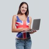 Muchacha británica sonriente con un ordenador portátil Imagenes de archivo