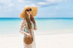 Muchacha bronceada atractiva en bikini azul y situación blanca del tunica en la costa El modelo hermoso toma el sol y se basa sob fotos de archivo