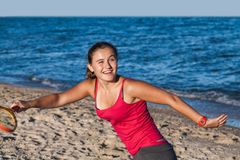 Muchacha bronceada delgada que juega a bádminton en la playa Foto de archivo libre de regalías