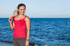 Muchacha bronceada delgada que juega a bádminton en la playa Imágenes de archivo libres de regalías