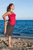 Muchacha bronceada delgada que juega a bádminton en la playa Fotografía de archivo libre de regalías