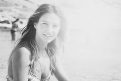 Muchacha bronceada hermosa en un bikini que se sienta en una playa rocosa Imágenes de archivo libres de regalías