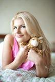 Muchacha cómoda joven en una cama con el juguete Fotografía de archivo libre de regalías