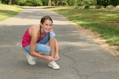 Muchacha cómoda joven que ata los zapatos en un parque Foto de archivo