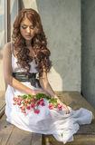 Muchacha cabelluda en un vestido de boda y maquillaje con un festivo con un ramo de rosas Fotos de archivo