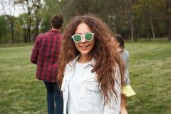 Muchacha cabelluda rizada en la sonrisa de las gafas de sol Imagen de archivo