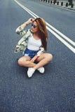 Muchacha californiana hermosa del inconformista que se sienta en su longboard del crucero en el medio de la carretera de asfalto Fotos de archivo libres de regalías